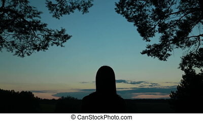 Young woman stretching towards the sky in the forest after sunset