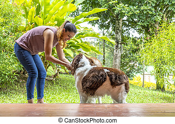 young woman stroking her two dogs in the garden of her house