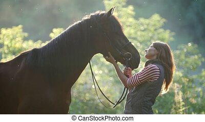 Young woman stroking horse's nose in the woods early in the...