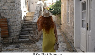 young woman strolls through the streets of an ancient European city