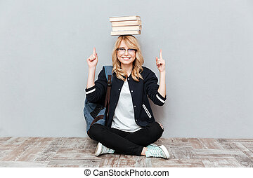 Young woman student holding books on head and pointing