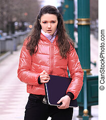 young woman student with laptop on the background of a winter city