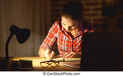 young woman student working on the computer at night
