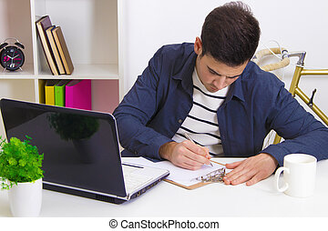 young woman studying at the desk with the laptop