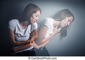 Young woman suffering from a severe depression/anxiety (color toned image; double exposure technique is used to convey the mood of unease, progression of the anxiety/depression)