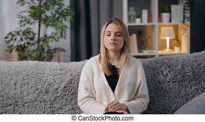 Young woman with blond hair sitting on grey couch and suffering from headache. Dissatisfied female having strong migraine at modern apartment.