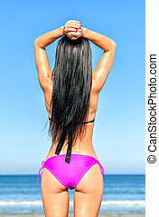 Young woman sunbathes at the beach. From the back.