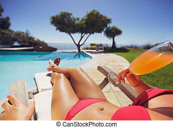 Young woman sunbathing by the poolside drinking fruit juice
