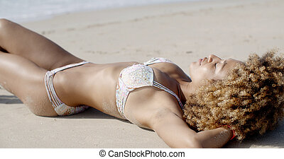 Young Woman Sunbathing In Bikini - Young woman sunbathing in...