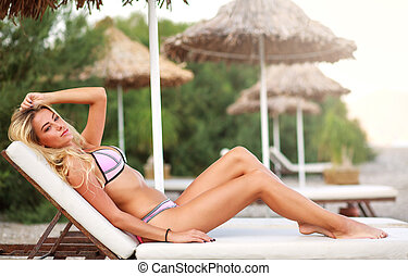 Young woman sunbathing lying on deckchair on beach...