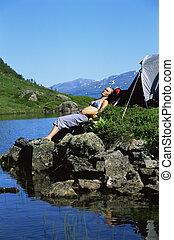 Young woman sunbathing on rocks next to lake