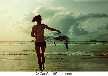 young woman surfer ready to surf on a beach
