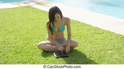 Young woman surfing on a tablet in the sun