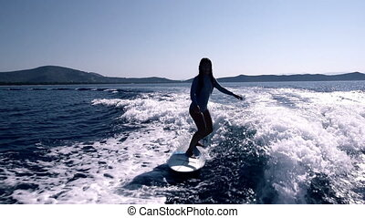 Young woman surfing - Blonde Surfer Girl Waving