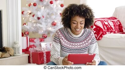 Young woman surfing the internet at Christmas sitting on the...