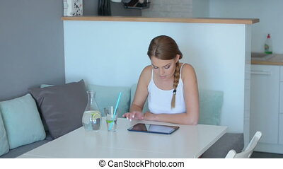 Young woman surfing the internet on a tablet