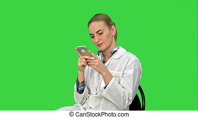 Young woman surgeon doctor reading sms on cell phone. Close up on a Green Screen, Chroma Key. 076. You can use it e.g. in your commercial video, business, medical presentation, broadcast video.