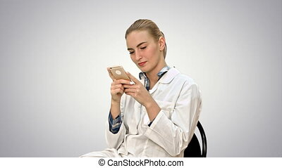 Young woman surgeon doctor reading sms on cell phone on white background.