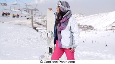 Young woman surveying the snow mountain slopes after...