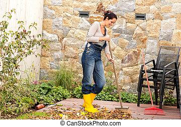 Young woman sweeping leaves veranda backyard happy