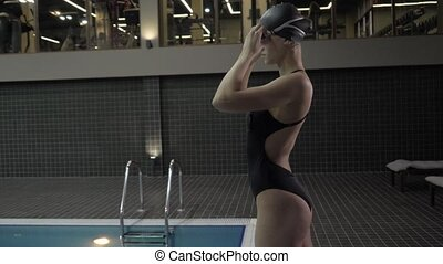 Young woman swimmer making warm up exercise for dive in...
