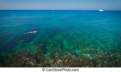 Young woman swimming in beautiful azure sea
