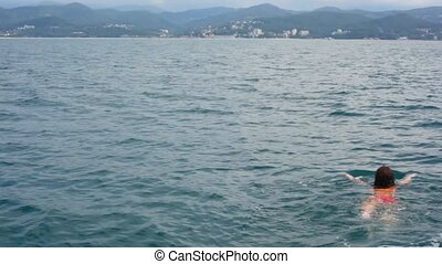 young woman swimming in sea from camera, mountain coast in background