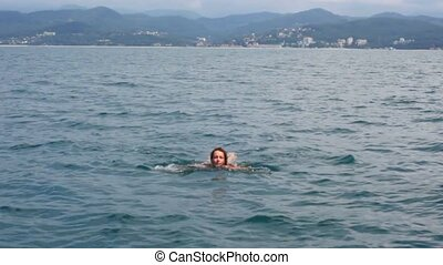 young woman swimming in sea to camera, mountain coast in background