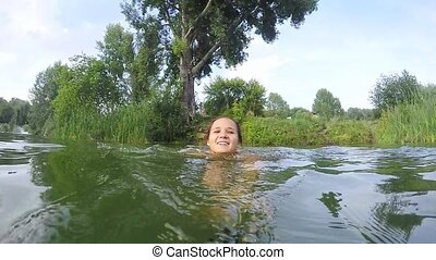 Young woman swimming in the lake in slow motion.