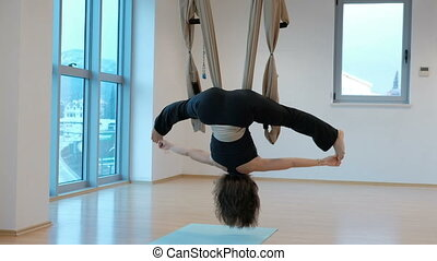 Young woman swings upside down in hammock studio indoors.