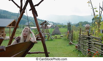 Young woman take a rest on the big woode swing
