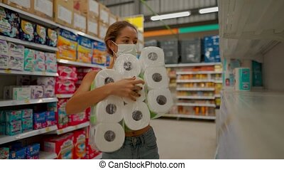 young woman wearing protect mask takes pack of toilet paper in shop with empty shelves
