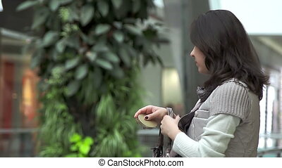 Young woman take powder box and look into small glass