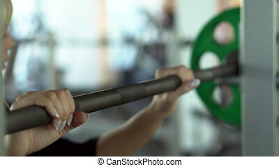 young woman takes a barbell on her shoulders before a...