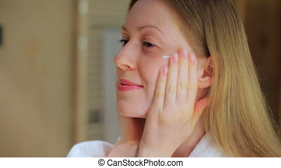 Young woman takes care of her face.