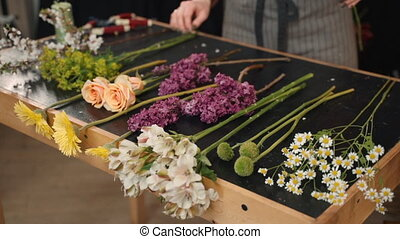 Young woman takes flowers in her hands to create composition while standing in workshop.