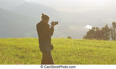 Young woman takes picture of Mountains Landscape in the...