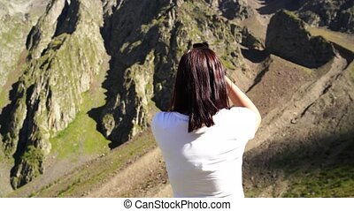 Young woman takes pictures of mountain landscape on smartphone. Female tourist photographing mountains on mobile phone.