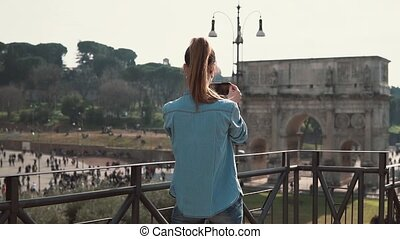 Young woman takes pictures of the arch of Constantine with her smartphone in Rome, Italy in a sunny day. Slow motion.