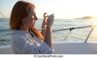 Young woman takes pictures on the camera phone during a boat ride on the boat