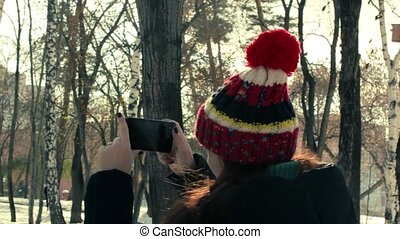 young woman takes video on your smartphone in the winter park
