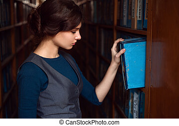 Young woman taking a book from library shelf.