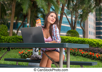 Young woman taking a break to relax from work on the laptop in park while holding cup of coffee in one hand with her eyes closed and smile pleasure