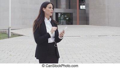 Young woman taking a call using earplugs