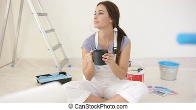Young woman taking a coffee break while redecorating her...