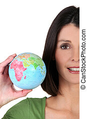 young woman taking a little globe in her hand