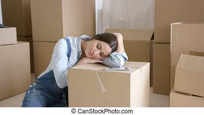 Young woman taking a nap on a brown carton as she relaxes...