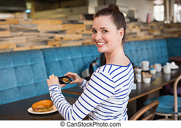 Young woman taking a photo of her lunch