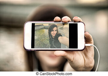 Young woman taking a photo with her phone