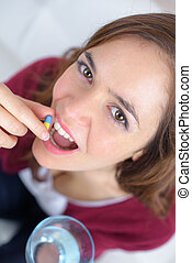 young woman taking a pill